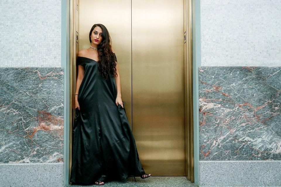 Sahar is wearing the Eugene Taylor black v-neck shoulder dress | Photo by Clyde Munroe