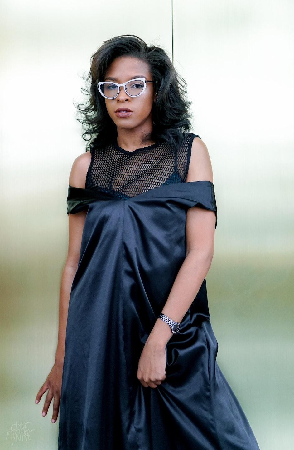Tayler is wearing the Eugene Taylor black v-neck shoulder dress | Photo by Clyde Munroe